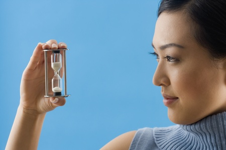 Asian woman looking at hourglass