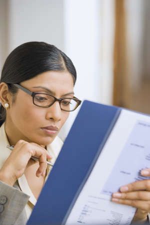 only one young adult woman: Indian businesswoman reading paperwork