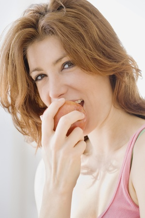 mischievious: Woman eating apple