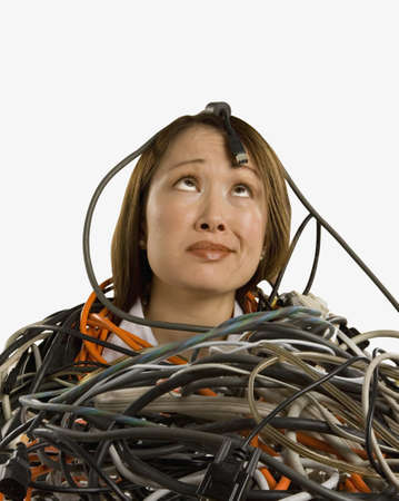 Studio shot of Asian woman buried in computer cables Stock Photo