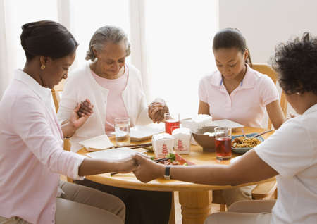 gramma: African family holding hands and praying at dinner table