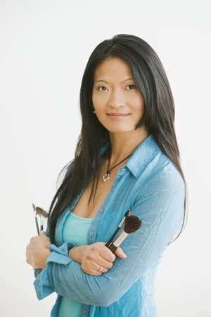 mid life: Studio shot of Asian woman holding makeup brushes