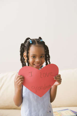 African girl holding paper heart