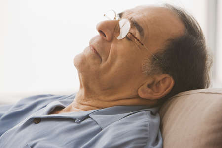 slumbering: Close up of senior Hispanic man sleeping on sofa