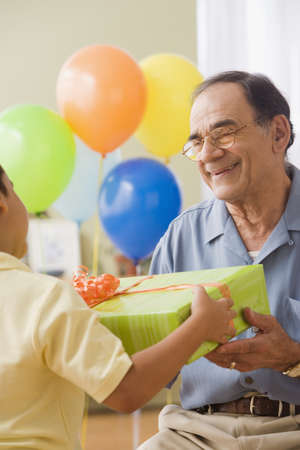 wearying: Hispanic grandfather and grandson exchanging birthday gifts