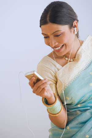1 person: Indian woman in traditional clothing using mp3 player