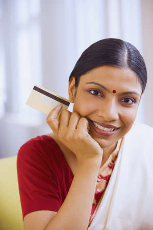 demure: Indian woman in traditional clothing holding credit card