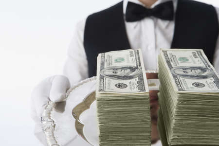 interrogating: Close up of stacks of money on silver platter