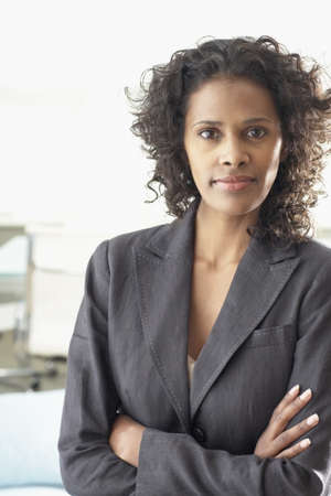 jamaican ethnicity: African businesswoman standing with arms crossed LANG_EVOIMAGES
