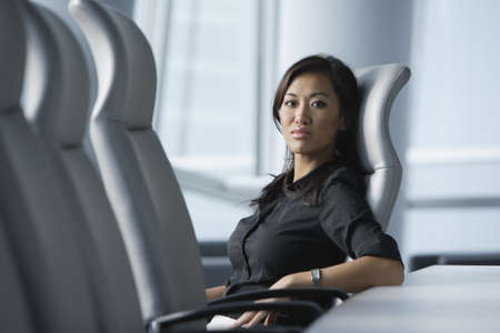 jamaican adult: Asian businesswoman sitting in conference room