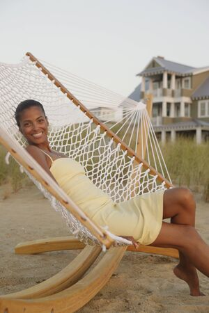 casualness: African woman sitting in hammock at beach