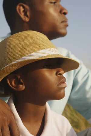 fathering: Close up of African father and son at beach LANG_EVOIMAGES