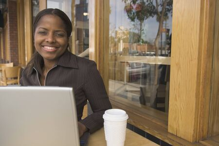 german ethnicity: African businesswoman with laptop at cafe