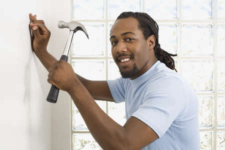 unconcerned: African man hammering nail into wall