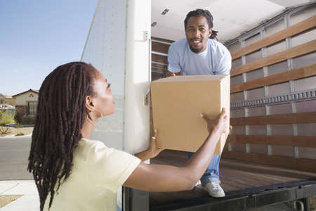 poppa: African man handing box to woman out of moving truck