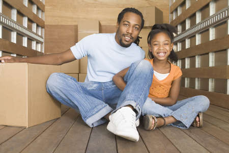 African father and daughter smiling in back of moving truck Stock Photo