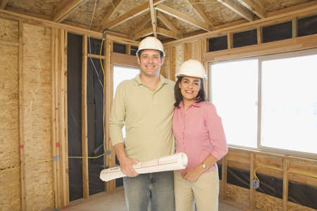 conferring: Couple in hard hats with blueprints on construction site