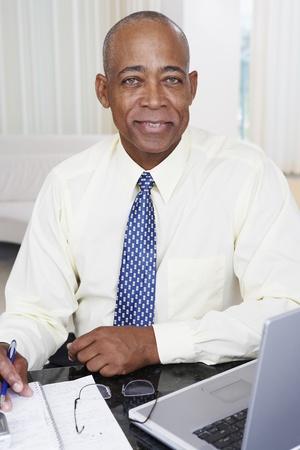 Senior Afrikaanse zakenman met laptop op het bureau
