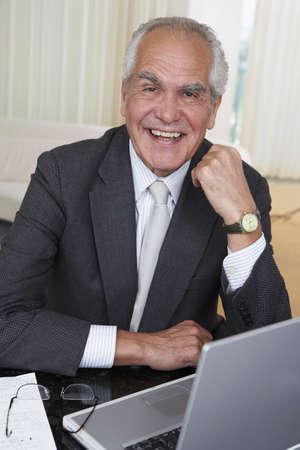 Senior businessman with laptop at desk