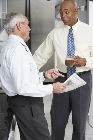 connexion: Two senior businessmen talking in break room