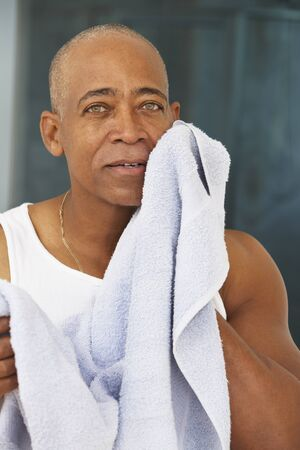 Senior African man drying face with towel