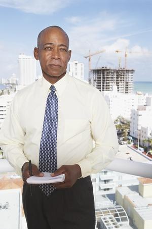 eyes downcast: Senior African businessman on balcony