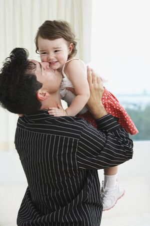 Hispanic father holding up and kissing young daughter Imagens - 35678416