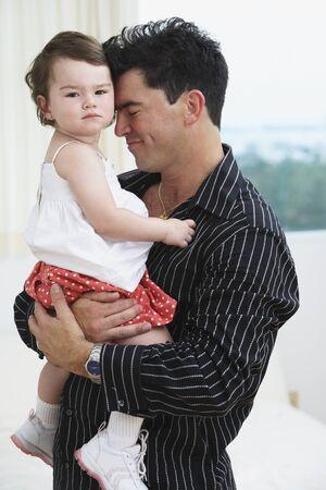 bambino: Hispanic father hugging young daughter