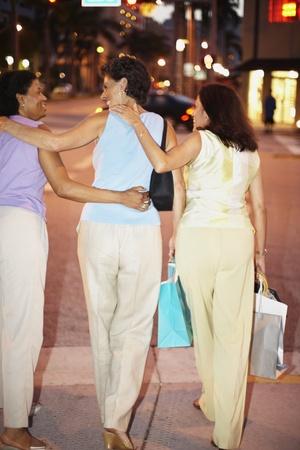 bambino: Rear view of Hispanic women walking on sidewalk with shopping bags