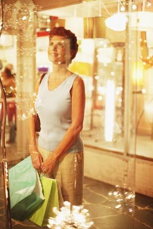 sidewalk talk: Hispanic woman with shopping bags looking in shop window