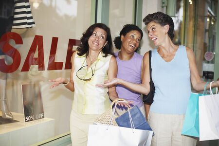 Hispanic women shrugging shoulders next to shop with sale sign