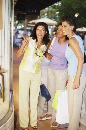 acknowledging: Hispanic women window shopping holding shopping bags