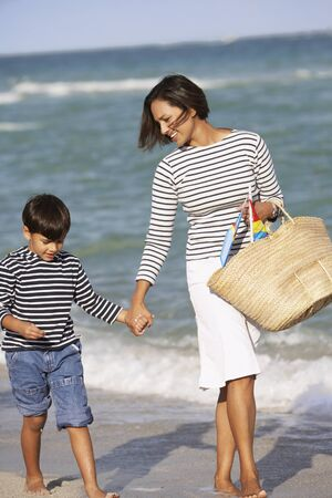 woman s bag: Indian mother and son holding hands and walking on beach LANG_EVOIMAGES