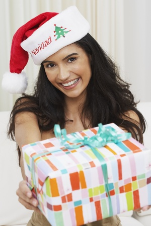 french ethnicity: Hispanic woman wearing Santa hat and holding out gift