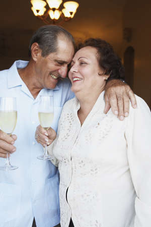 unyielding: Senior couple hugging and drinking glasses of champagne