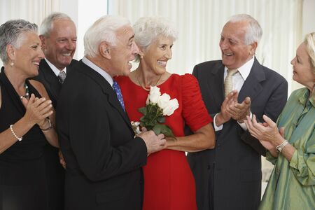 Senior man giving wife bouquet of flowers while friends clap