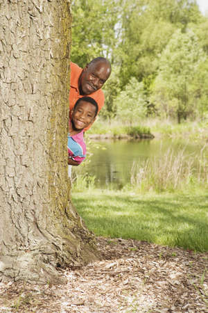 portraiture: African grandfather and grandson peeking out from behind tree in park LANG_EVOIMAGES