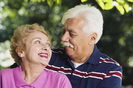 Senior Hispanic couple smiling at each other