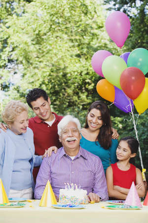 Senior Hispanic man with family and birthday cake Stock Photo