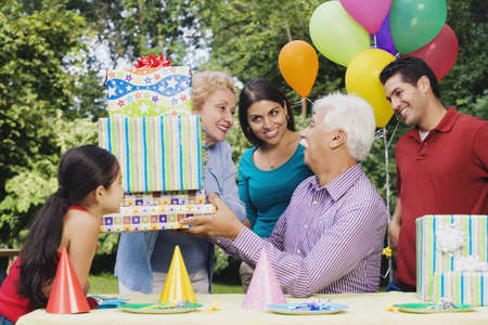 generation gap: Senior Hispanic man receiving gifts at birthday party