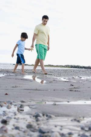 gramma: Hispanic father and son walking on beach with starfish