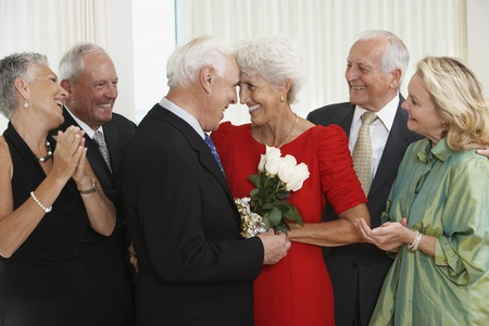 Senior man giving wife bouquet of flowers while friends watch 스톡 콘텐츠