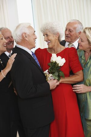 Senior man giving wife bouquet of flowers while friends watch Stock Photo