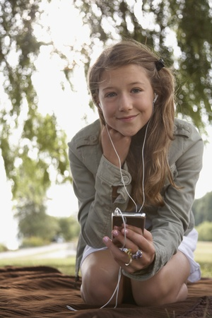 Teenage girl listening to mp3 player on blanket outdoors