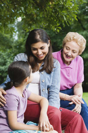 three generation: Hispanic grandmother, mother and daughter sitting together