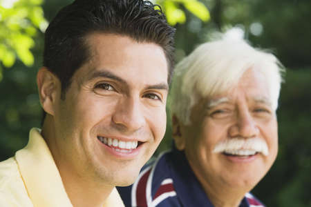 generation gap: Hispanic man smiling with father outdoors LANG_EVOIMAGES