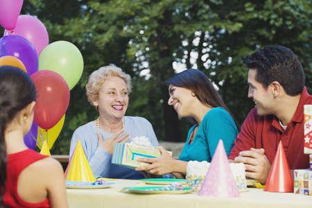Ältere hispanische Frau, die Geschenk auf Geburtstagsparty