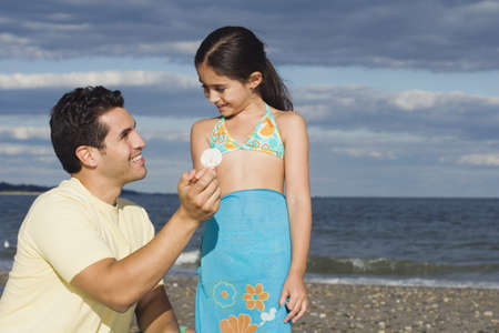 generation gap: Hispanic father and daughter looking at seashell