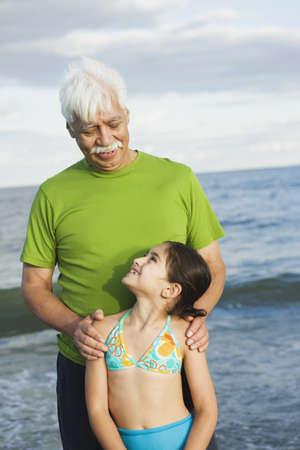 look latino: Hispanic grandfather and granddaughter at beach
