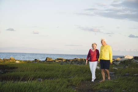 senior couple: Senior couple walking near ocean LANG_EVOIMAGES
